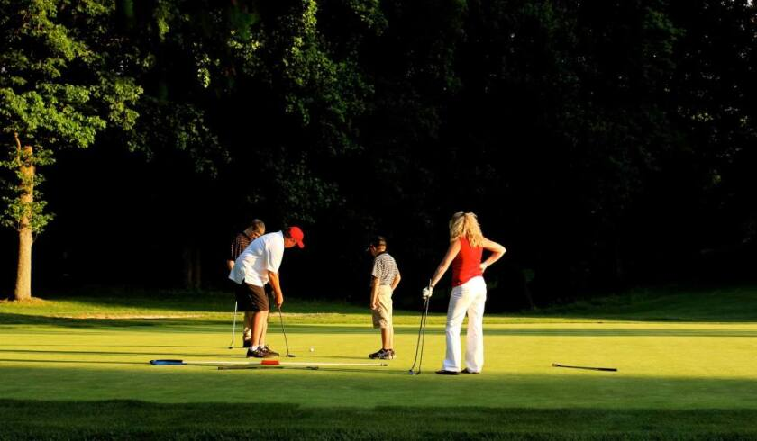 foursome putting on golf course