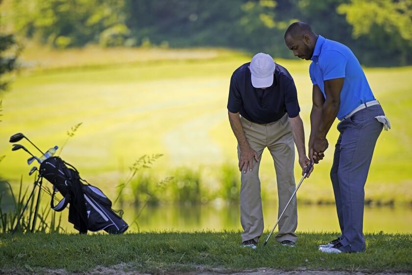 Golf Pro Teaching Male Golfer by pond