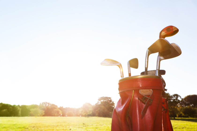 golf clubs in bag on golf course with sunshine